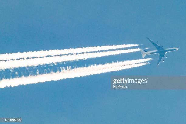 Lufthansa Boeing 747 overflying forming engine exhaust contrails behind in high altitude The iconic doubledecker Jumbo Jet is flying at 34000 feet...