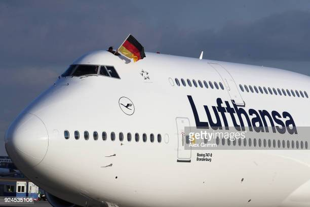 Lufthansa crew member waves a German flag during the welcome ceremony for the members of Team Germany after their return from the 2018 PyeongChang...