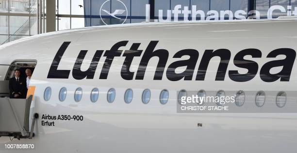 Lufthansa crew members stand at the door of the tenth Lufthansa Airbus A350900 during the naming ceremony of the aircraft on July 30 2018 at the...