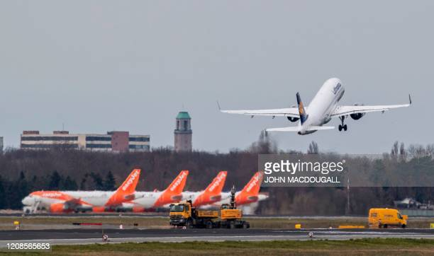 A Lufthansa plane takes off past aircraft of lowcost carrier Easyjet on the tarmac of Berlin's Tegel airport on March 30 amid a new coronavirus...