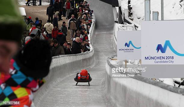A luge athelete races down the newly renovated Koenigssee ice track next to Munich 2018 candidate logos for the Olympic Winter Games during the Luge...