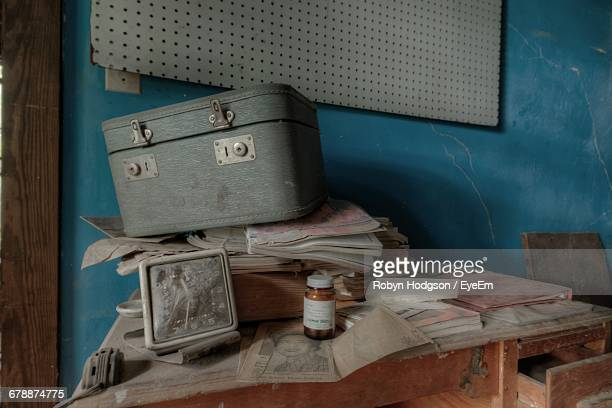 Luggage And Clock With Books On Table Against Wall In Abandoned House
