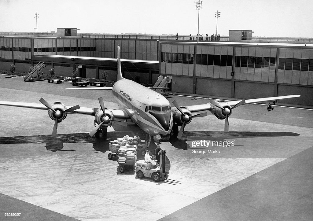 Luggage being unloaded from airplane : Stock Photo