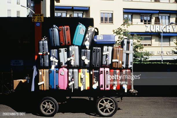 Luggage cart stacked with suitcases