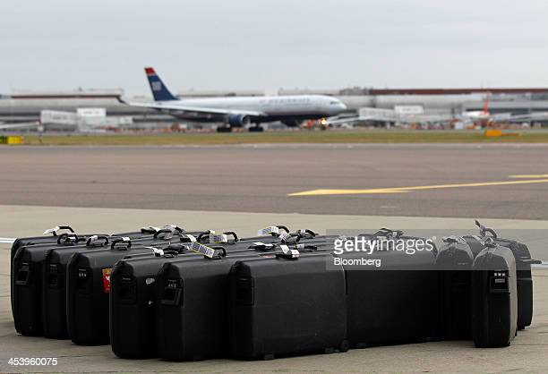 Luggage cases belonging to airline staff stand on the tarmac before being loaded onto an Airbus A380800 aircraft operated by Emirates at Terminal 3...