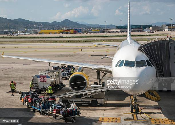 Luggage is being unloaded from a Vueling Airbus 320 airplane in El Prat Airport Barcelona Spain 06 September 2015 Vueling Airlines is a Spanish...