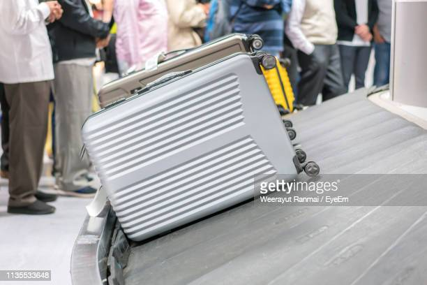 luggage on conveyor belt at airport - baggage claim stock pictures, royalty-free photos & images