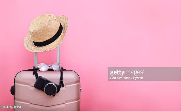luggage with hat against pink background - packing stock pictures, royalty-free photos & images