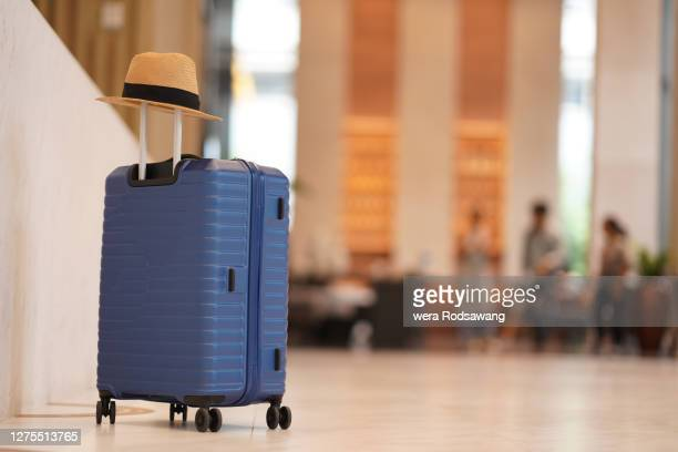 luggage with sun hat placing in front of hotel lobby isolated over hotel reception blurred background - suitcase stock pictures, royalty-free photos & images