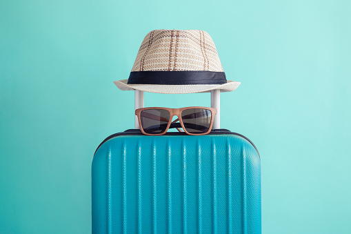 Luggage with woven beach hat and sunglasses on green background minimalistic vacation concept 945652968