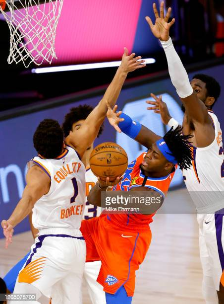 Luguentz Dort of the Oklahoma City Thunder passes around Devin Booker and Deandre Ayton of the Phoenix Suns during the third quarter at The Field...