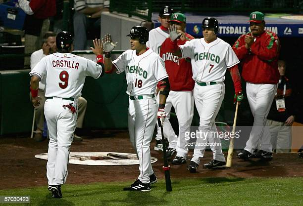 Luis A. Garcia of Team Mexico congratulates teammate Vinny Castilla after he scored on a wild pitch against Team South Africa during the Round 1 Pool...