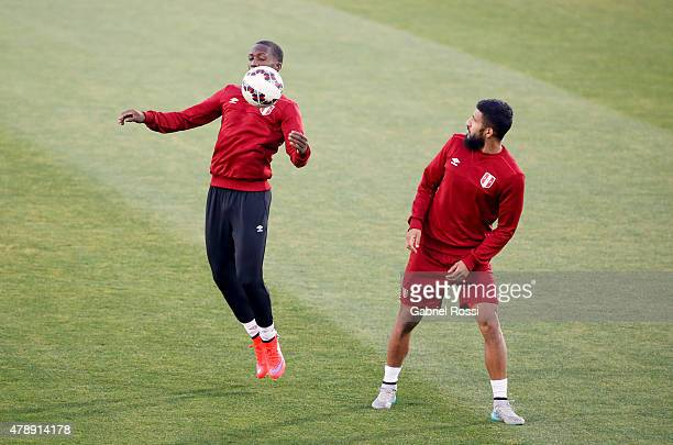 Luis Advincula of Peru controls the ball next to Josepmir Ballon of Peru during a field scouting prior to the semi final match against Chile at...
