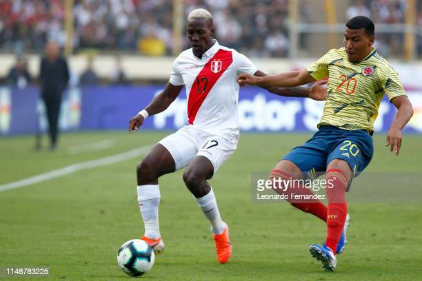 Luis Advincula of Peru fights for the ball with Roger Martinez of Colombia during a friendly match between Peru and Colombia at Estadio Monumental de...