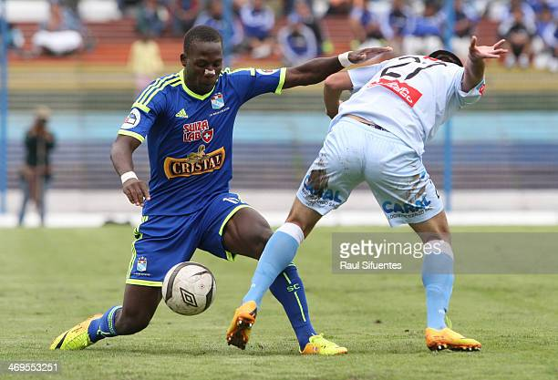 Luis Advincula of Sporting Cristal struggles for the ball with Ivan Santillan of Real Garcilaso during a match between Real Garcilaso and Sporting...