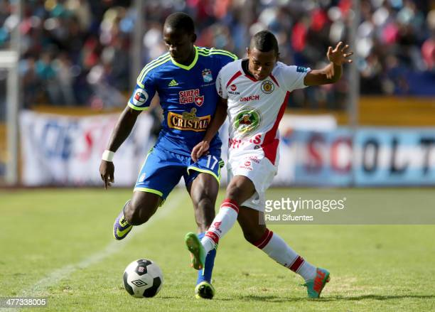 Luis Advincula of Sporting Cristal struggles for the ball with Jairsinho Gonzalez of Inti Gas during a match between Inti Gas and Sporting Cristal as...