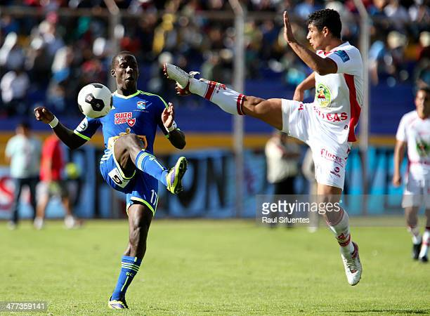 Luis Advinvula of Sporting Cristal struggles for the ball with Joseph Juarez of Inti Gas during a match between Inti Gas and Sporting Cristal as part...