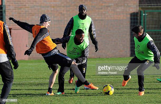 Luis Alberto and Raheem Sterling of Liverpool in action during a training session at Melwood Training Ground on December 24 2013 in Liverpool England