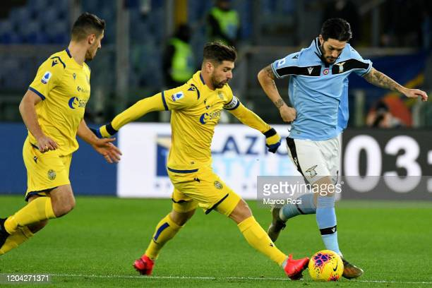 Luis Alberto of SS Lazio compete for the ball with Miguel Veloso of Hellas Verona during the Serie A match between SS Lazio and Hellas Verona at...