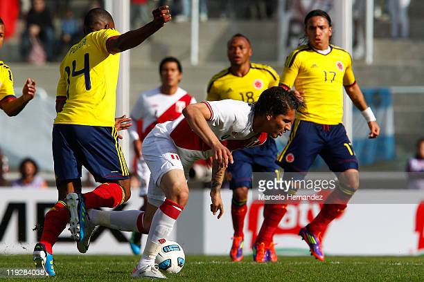 Luis Amaranto Perea of Colombia struggles for the ball with Jose Paolo Guerrero of Peru during a quarter final match between Colombia and Peru as...