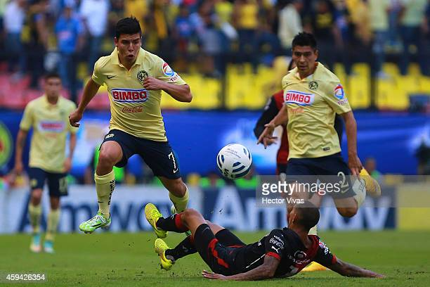 Luis Angel Mendoza of America struggles for the ball with Edgar Castillo of Atlas during a match between America and Atlas as part of 17th round...