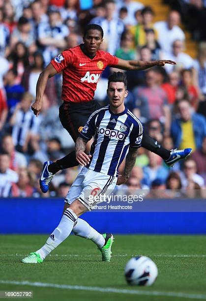 Luis Antonio Valencia of Manchester United crosses the ball past Liam Ridgewell of West Bromwich Albion for Jonas Olsson of West Bromwich Albion to...