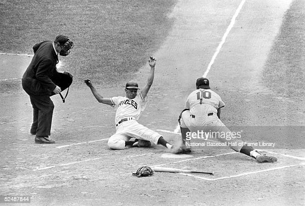 Luis Aparicio of the Baltimore Orioles slides into home as Earl Battey of the Minnesota Twins tries to block the plate during a 1963 season game