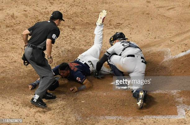 Luis Arraez of the Minnesota Twins slides safely into home plate against Austin Romine of the New York Yankees as umpire David Rackley looks on...