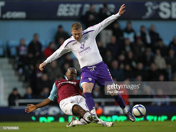 Luis Boa Morte of West Ham United tackles Garry O'Connor of Barnsley during the FA Cup sponsored by E.O.N 3rd Round match between West Ham United and...