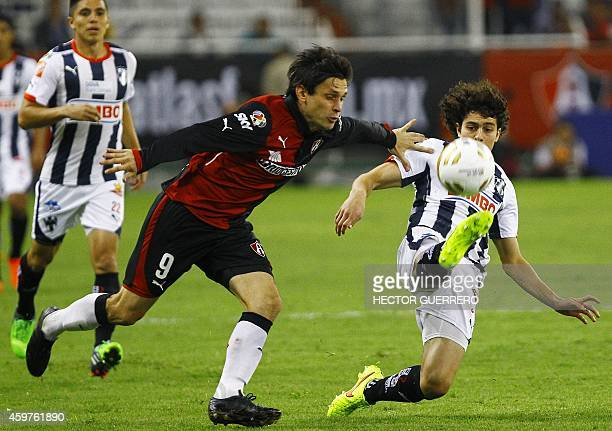 Luis Caballero of Atlas vies for the ball with John Medina of Monterrey during a 2014 Mexican Apertura tournament football match in Guadalajara...