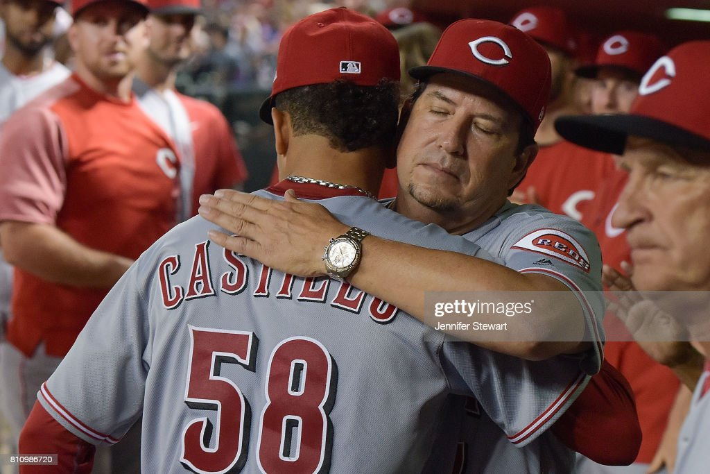 Luis Castillo #58 of the Cincinnati Reds is hugged by pitching coach Mack Jenkins #57 after being relieved during the seventh inning of the MLB game against the Arizona Diamondbacks at Chase Field on July 8, 2017 in Phoenix, Arizona.