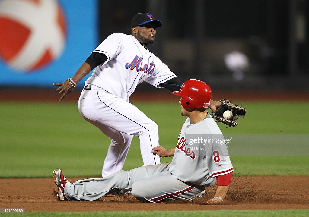 Luis Castillo #1of the New York Mets is late with the tag on a stolen base by Shane Victorino #8 of the Philadelphia Phillies during their game on May 27, 2010 at Citi Field in the Flushing neighborhood of the Queens borough of New York City.