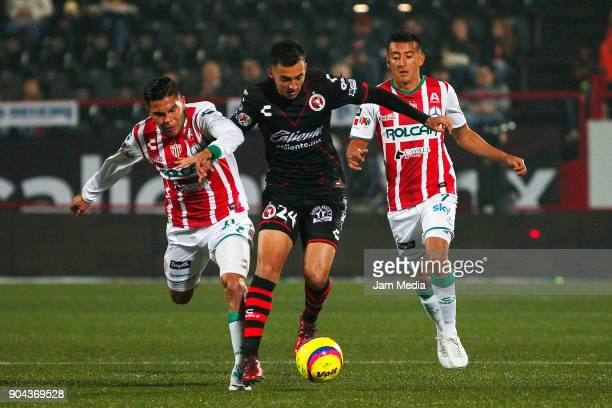 Luis Chavez of Tijuana fights for the ball with Luis Perez Daniel Alvarez of Necaxa during the second round match between Tijuana and Necaxa as part...