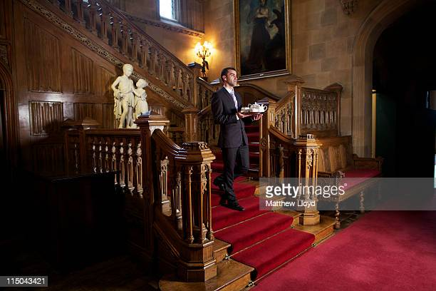 Luis Coelho, Banqueting Manager, serves tea on the oak staircase in Highclere Castle on March 15, 2011 in Newbury, England. Highclere Castle has been...