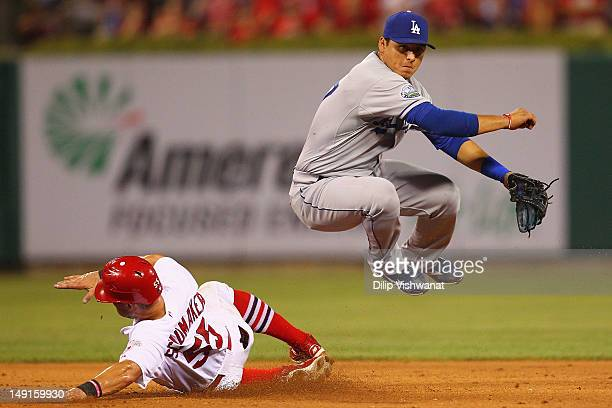 Luis Cruz of the Los Angeles Dodgers turns a double play over Skip Schumaker of the St. Louis Cardinals at Busch Stadium on July 23, 2012 in St....
