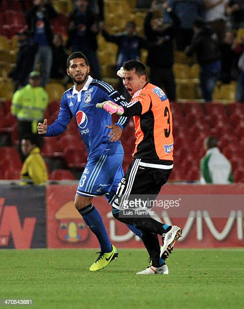 Luis Delgado goalkeeper of Millonarios and Oswaldo Henriquez celebrate after taking a penalty kick to score the first goal during a match between...
