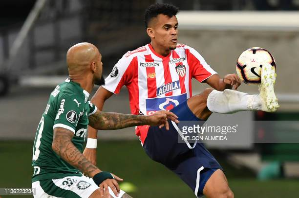 Luis Diaz of Colombia's Junior vies for the ball with Felipe Melo of Brazil's Palmeiras during their 2019 Copa Libertadores football match held at...