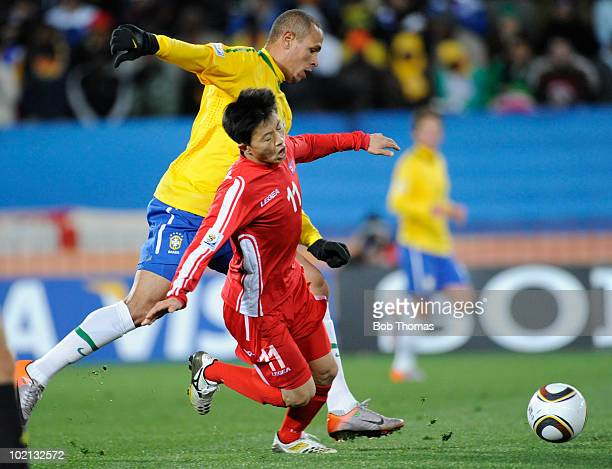 Luis Fabiano of Brazil and Mun In Guk of North Korea battle for the ball during the 2010 FIFA World Cup South Africa Group G match between Brazil and...
