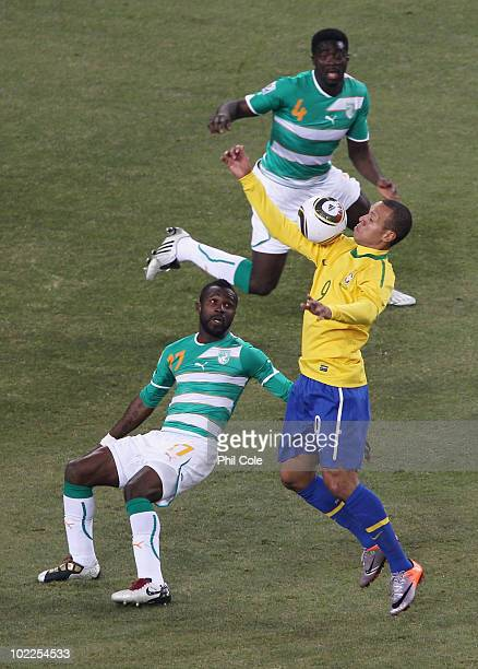 Luis Fabiano of Brazil controls the ball before scoring the second goal as Siaka Tiene and Kolo Toure of the Ivory Coast look on during the 2010 FIFA...