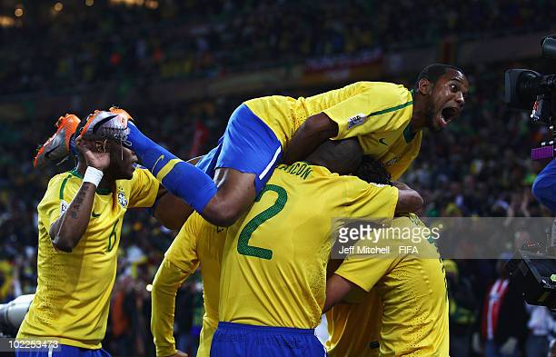 Luis Fabiano of Brazil is mobbed by Robinho and team mates celebrating after scoring the opening goal during the 2010 FIFA World Cup South Africa...
