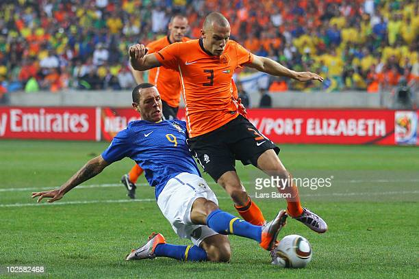 Luis Fabiano of Brazil tackles John Heitinga of the Netherlands during the 2010 FIFA World Cup South Africa Quarter Final match between Netherlands...