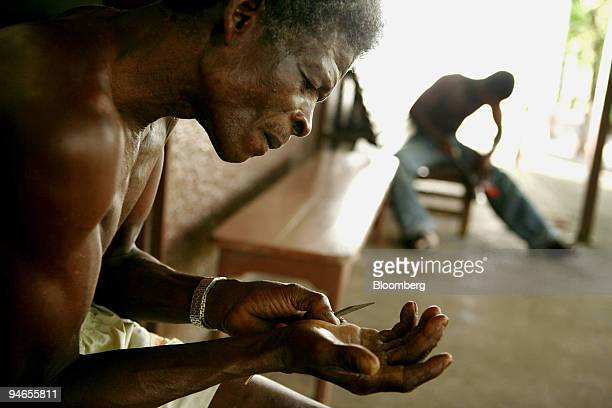 Luis Fernando Perilla Mosquera pulls thorns from his hand while sitting in front of his room at Hacienda Napoles the favored recreation home of the...