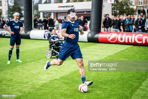 Luis Figo kicks a ball with a mask to feel like a blind player during the EqualGame Match at the Fan Zone ahead of the UEFA Europa League Final...
