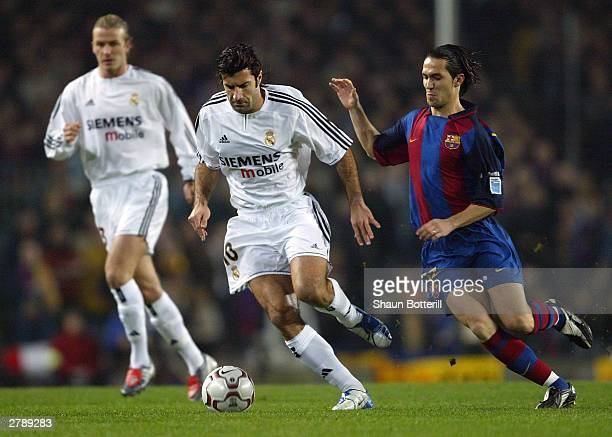 Luis Figo of Real Madrid is challenged by Luis Garcia of Barcelona during the Spanish Primera Liga match between Barcelona and Real Madrid at the Nou...