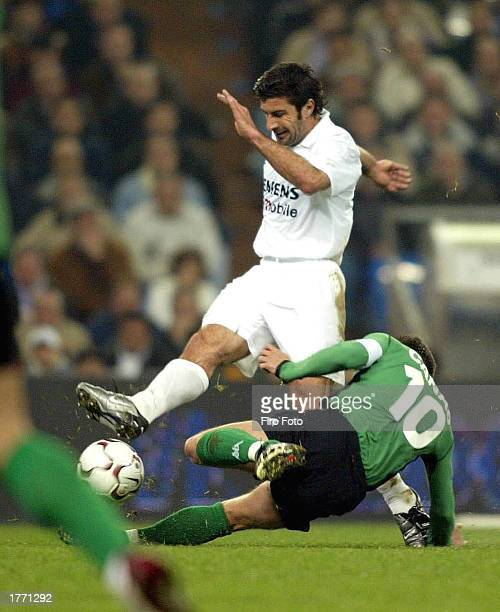 Luis Figo of Real Madrid is tackled by Canas of Betis during the La Liga match between Real Madrid and Real Betis played at the Santiago Bernabeu...