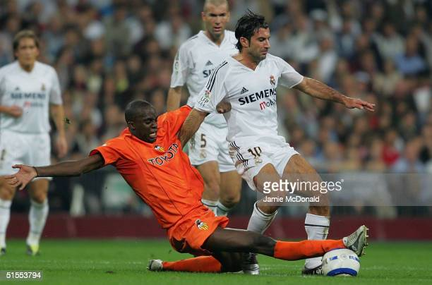 Luis Figo of Real Madrid is tackled by Sissoko of Valencia during the La Liga match between Real Madrid v Valencia at the Bernabau stadium on October...