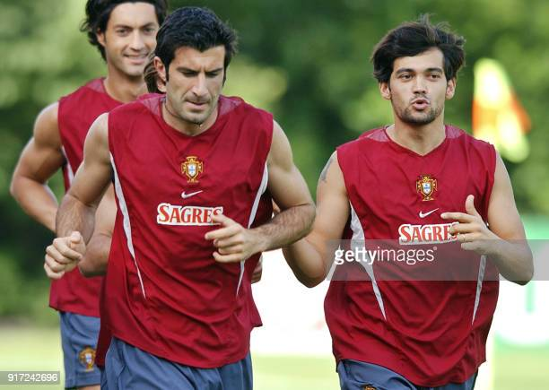 Luis Figo Sergio Conceicao and Vitor Baia run warm up laps during a training session at a local soccer field in eastern Seoul 11 June 2002 Portugal...