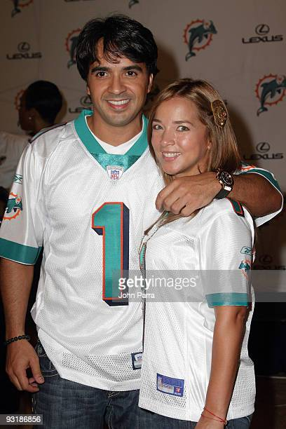 Luis Fonsi and Adamari Lopez attend the Dolphins game at Landshark Stadium on October 12 2009 in Miami Florida