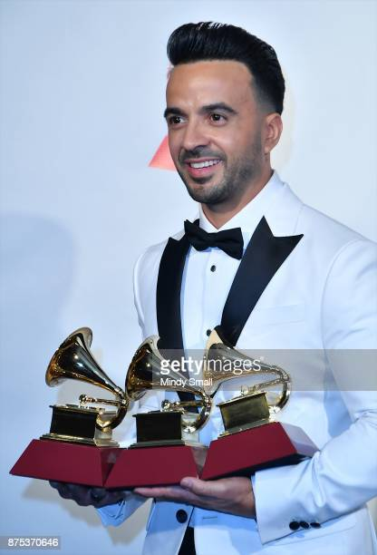 Luis Fonsi poses with awards for Song of the Year and Record of the Year in the press room during The 18th Annual Latin Grammy Awards at MGM Grand...