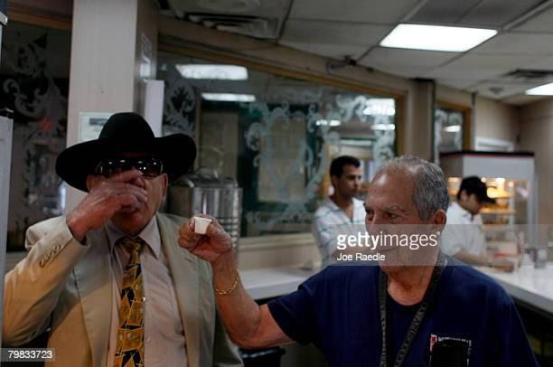 Luis Garcia and Alfredo Garcia Menocal drink their morning coffee at the Versailles restaurant in the Little Havana neighborhood February 19, 2007 in...